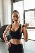 Barna sportos nő kezével csípő edzés súlyzóval és nézi a kamera tornaterem