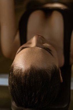Selective focus of brunette sportswoman lying on sport equipment stock vector