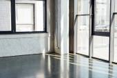 Denní světlo přes okna ve sportovním centru s šedou podlahou