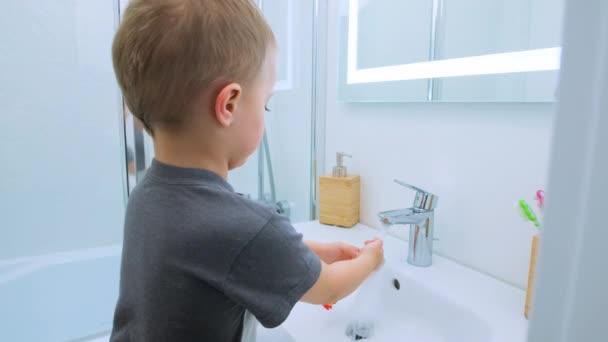 Kaukasischer Junge im grauen T-Shirt wäscht im hellweißen Badezimmer auf einem kleinen Stuhl eine Zahnbürste unter dem Wasserhahn. Wasseraktivitäten, Hygiene, Kinderbetreuung