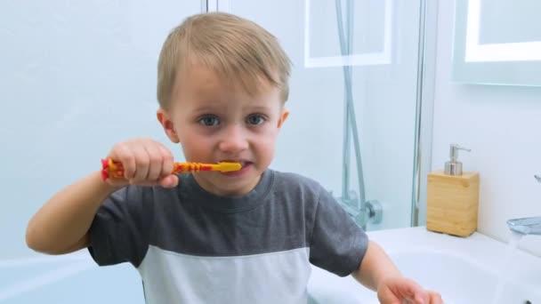 Šťastné dítě si čistí zuby. Dítě s úsměvem ukazuje zuby do fotoaparátu ve světle bílé koupelně, zatímco stojí na malé židli. Vodní aktivity, hygiena, péče o děti