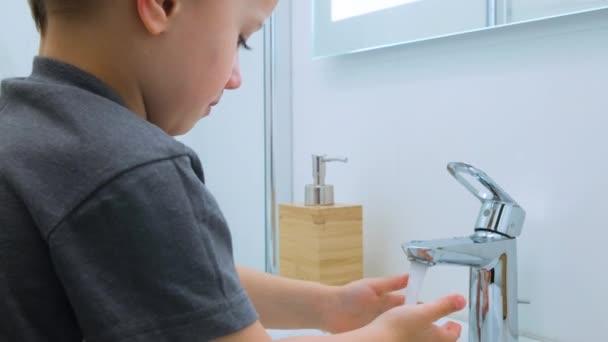 Kaukasisches Kind im grauen T-Shirt dreht das Wasser im Waschbecken an, wäscht sich die Hände unter einem Wasserstrahl im hellweißen Badezimmer. Wasseraktivitäten, Hygiene, Kinderbetreuung