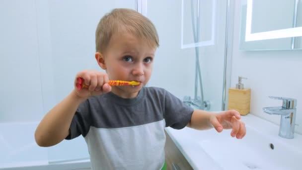 Šťastný chlapec si čistí zuby. Dítě s úsměvem ukazuje své žvýkané zuby rodičům ve světle bílé koupelně, když stojí na malé židli. Vodní aktivity, hygiena, péče o děti