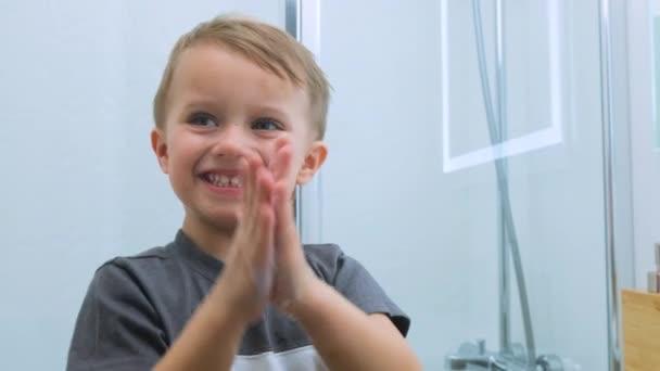 Großaufnahme eines kaukasischen Kindes in einem grauen T-Shirt, das seine Hände einseift und auf saubere Handflächen im hellweißen Badezimmer blickt. Wasseraktivitäten, Hygiene, Kinderbetreuung