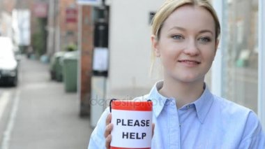 Young Woman Collecting Money For Charity In Street