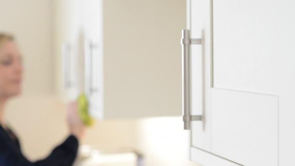 Érett nő, tisztítás konyha szekrények otthon