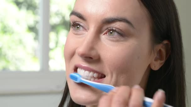 Woman In Bathroom Brushing Teeth With Manual Toothbrush