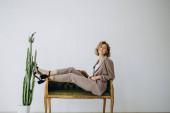 Egy vonzó szőke nő portréja, aki egy női ruhaüzlet reklámjában pózol zakóban, nadrágban és cipőben.