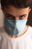 Egy maszkot viselő fiatalember karanténban van otthon.