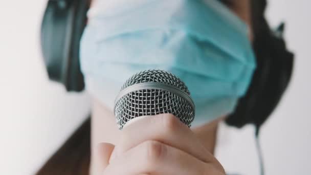 Mladý zpěvák zpívající v mikrofonu fith face mask v domácím studiu. Vzdálená práce, sebeizolace a prevence šíření koronaviru