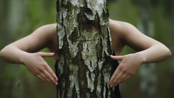 Mladá šťastná běloška objímající strom v lese a vytvářející trojúhelník s rukama