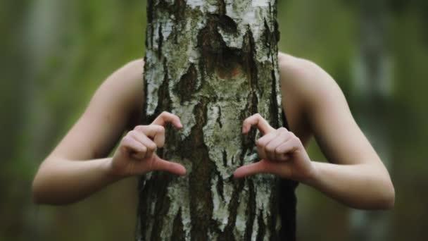 Láska k přírodě. Mladá žena objímající strom a tvořící se tvar srdce rukama