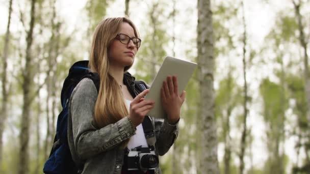Fiatal kaukázusi nő hátizsákos használja tabletta a tájékozódás az erdőben. Alacsony szögű lövés