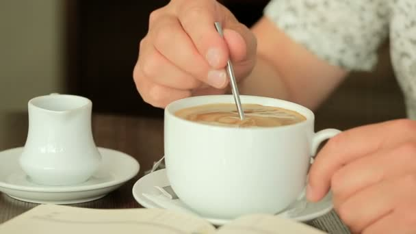 man mixing sugar in coffee cup