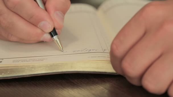 male hand writing in a notebook, close-up