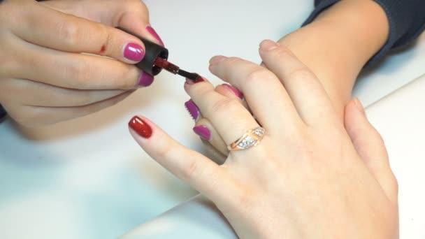 Kosmetikerin lackiert Nägel von Frauen