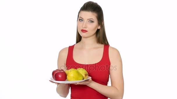žena držící desku s červenými jablky a hruškami a usmívá se