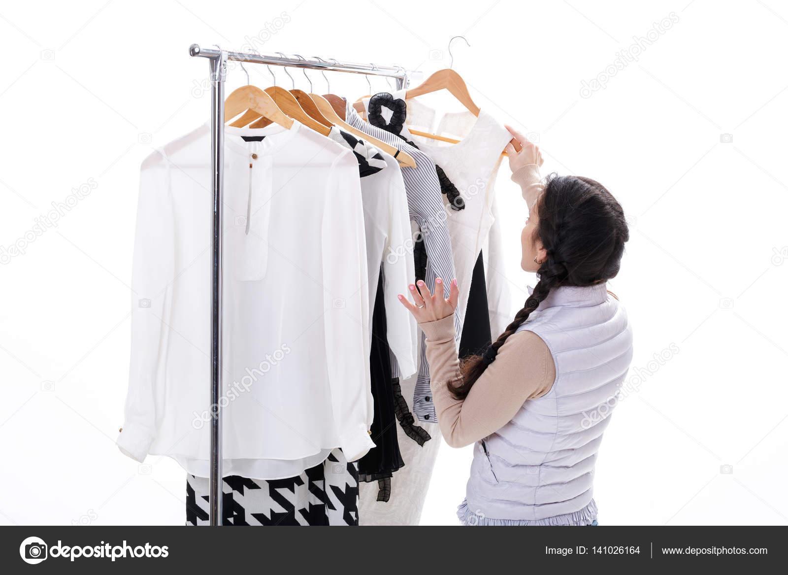 b7f65616feea ΕΜΠ — Φωτογραφία Αρχείου · Γυναίκα επιλέγει νέα μόδα ρούχα στις ξύλινες  κρεμάστρες στο ράφι σε άσπρο φόντο. Ψώνια έννοια — Εικόνα από erstudio