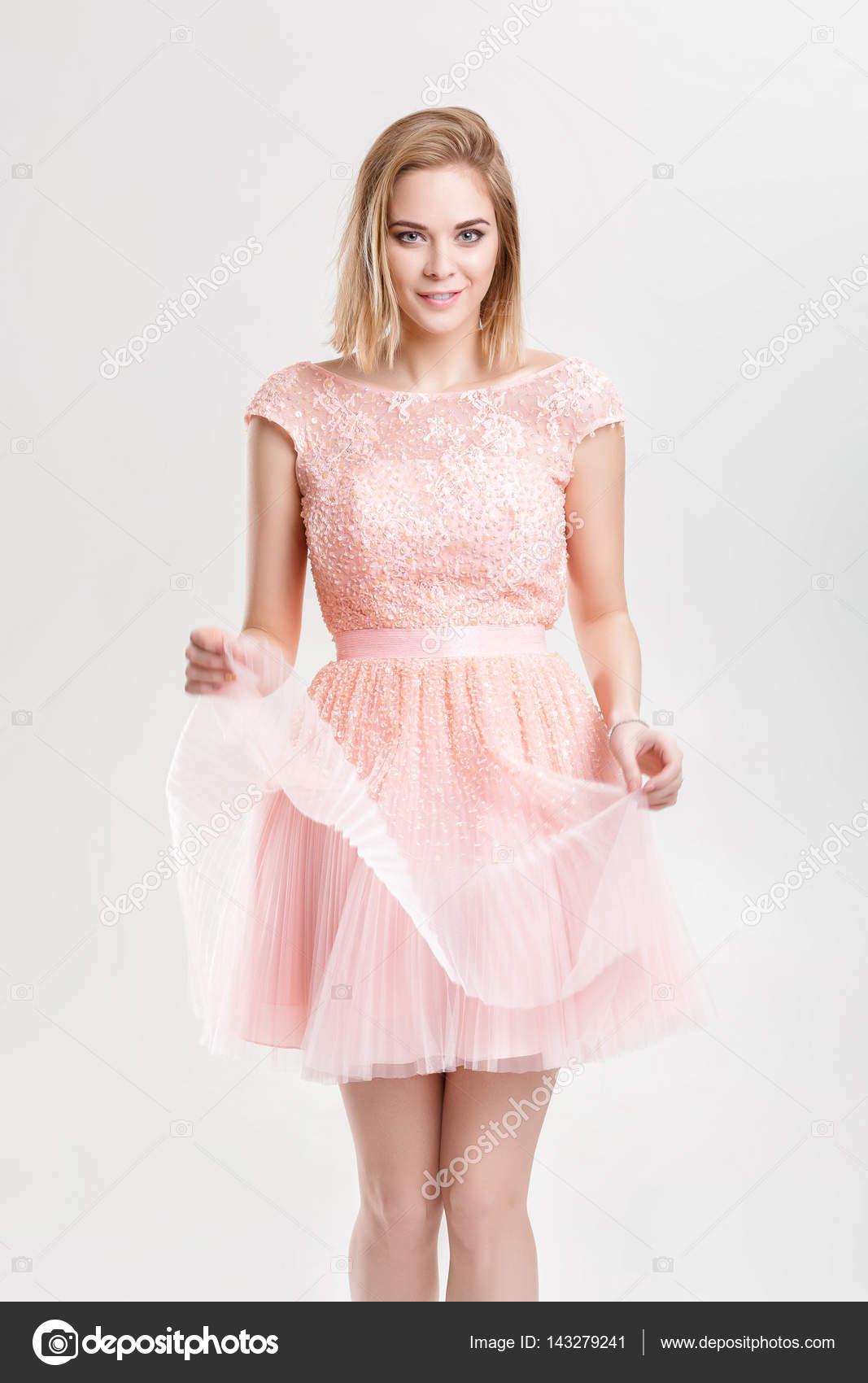 hermosa mujer rubia en un vestido de Cóctel rosa bailando y havin ...