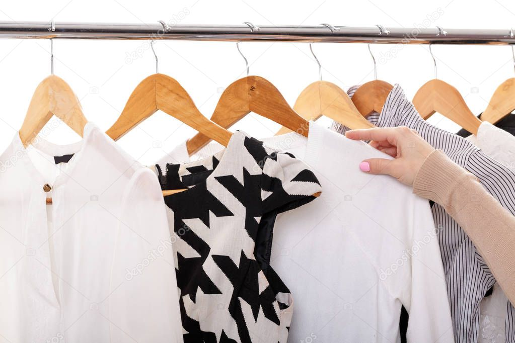 6a73c63d76a5 γυναικείο χέρι επιλέγει νέα μόδα ρούχα στις ξύλινες κρεμάστρες στο ράφι — Φωτογραφία  Αρχείου © erstudio  145074283