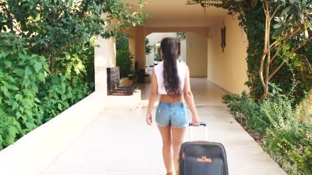 Jovem morena bronzeada em shorts, óculos de sol vem com mala no hotel, no  verão. férias e férias– gráficos de vetor dac1e46b29