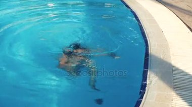 Mladá brunetka žena v bikinách ponory v bazénu na letní slunečný den