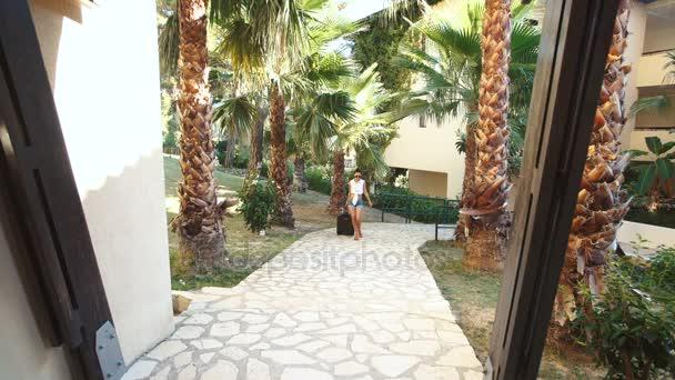 Mladá brunetka žena v šortkách, sluneční brýle a podpatky přichází s kufrem mezi palmami v hotelu. dovolená
