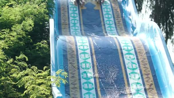 Happy couple sliding down water slide smiling in sunny summer. water Park. Slow motion