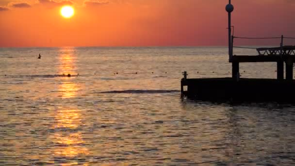 krásný západ slunce na moři. silueta člověka skákat z mola do Středozemního moře