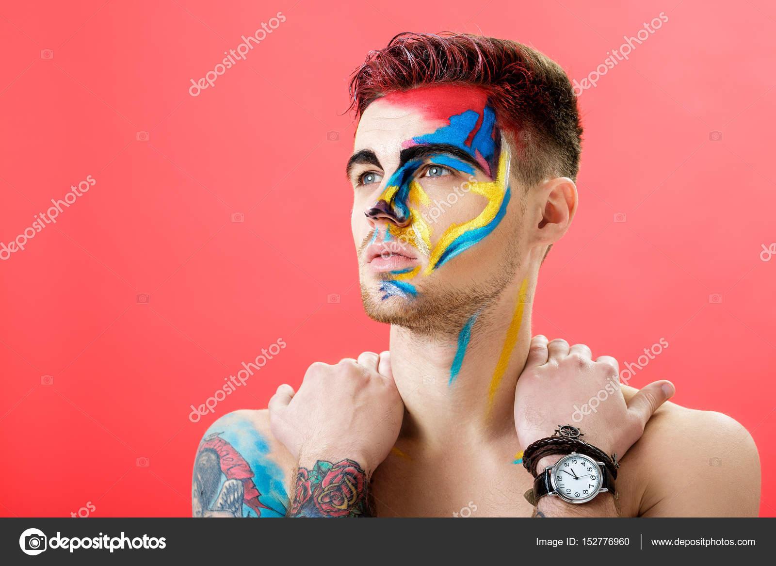 Kırmızı Bir Arka Plan üzerinde Renkli Yüz Boyama Ile Genç Adam