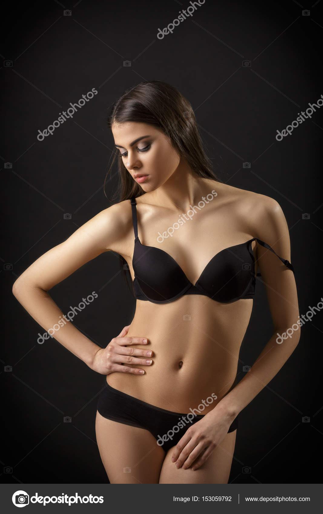 cd3377478 Bela mulher sexy morena posar em lingerie preta sobre fundo preto. Sedutor  e atraente slim