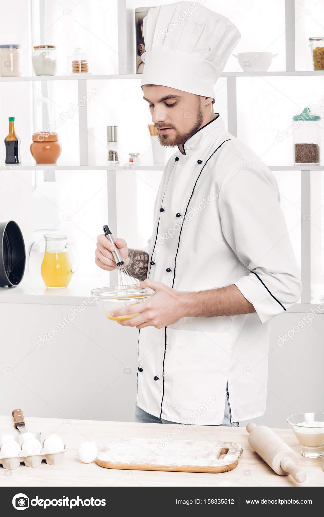 Koch in Uniformen, Auspeitschen, Eiern und Milch in Schüssel in ...