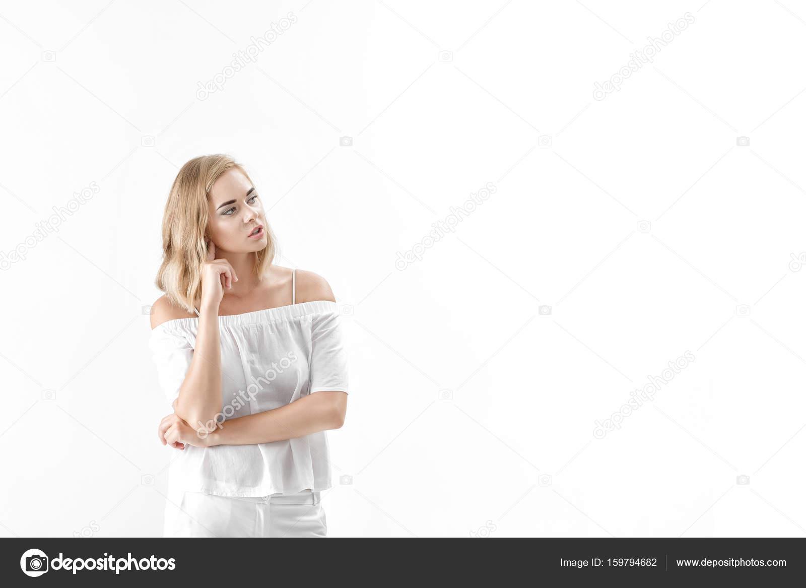 Schöne blonde Frau in weißer Bluse und Hose auf weißem Hintergrund ...