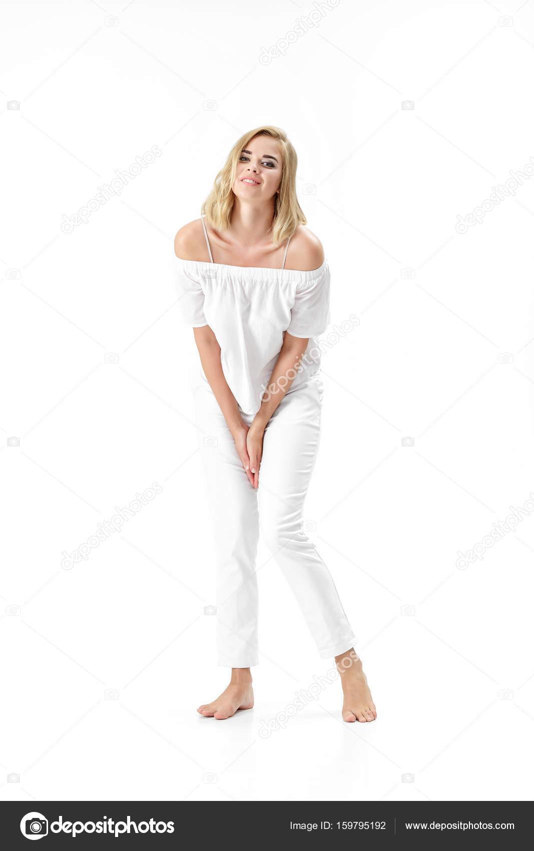 Schönen lächelnden blonden Frau in weißer Bluse und Hose auf weißem ...