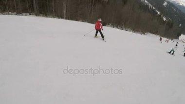 Skiers skiing down on slopes in Bukovel ski resort.