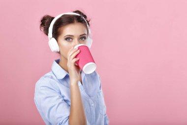 woman in headphones drinking coffee