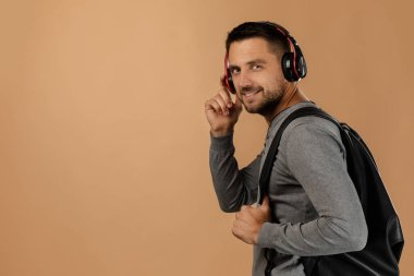 handsome young man with headphones and backpack