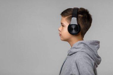 Happy child boy enjoys listens to music in headphones