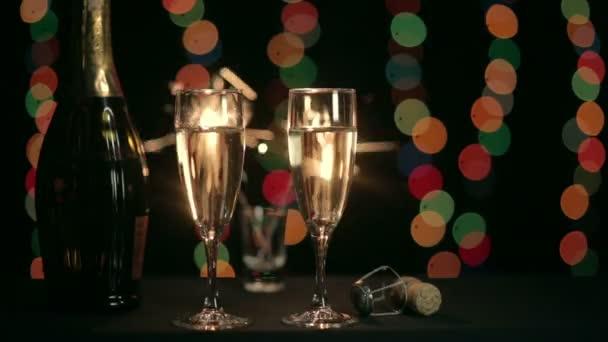 Dvě sklenice šampaňského na pozadí hořícího prskavka