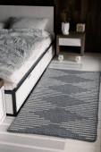 Kötött szürke téglalap alakú szőnyeg az ágy hátoldalán és fa éjjeliszekrények. A belső tér a hálószoba skandináv stílusban és nyugodt természetes tónusok.
