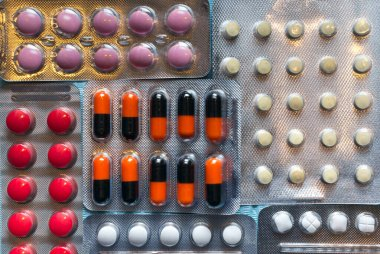 Multicolored tablets and capsules in blisters close-up, top view. The concept of treating human diseases.