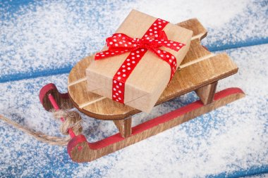 Wooden sled and wrapped gift for Christmas or other celebration on snowy boards