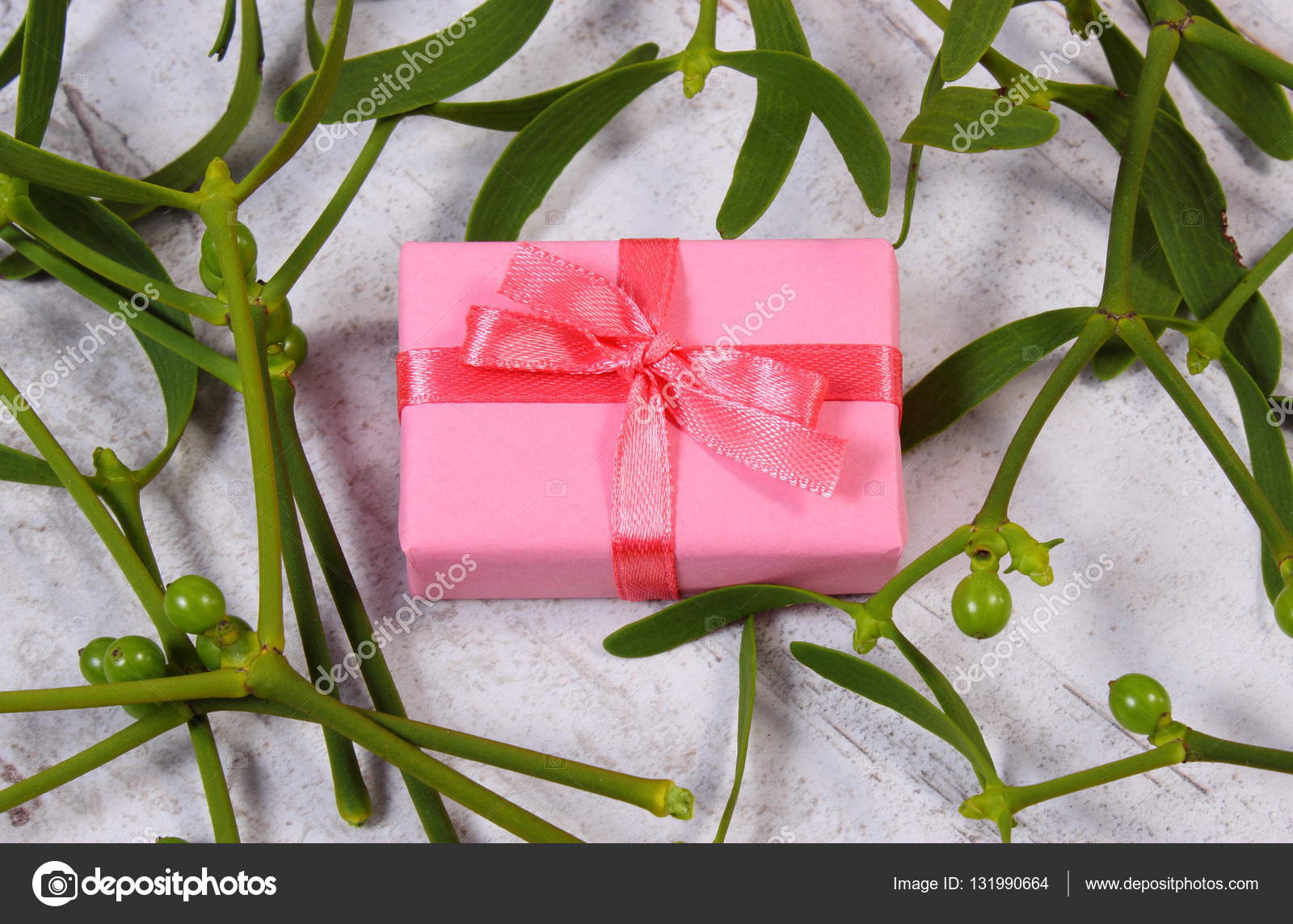 Wrapped pink gift for Christmas and mistletoe on old wooden ...