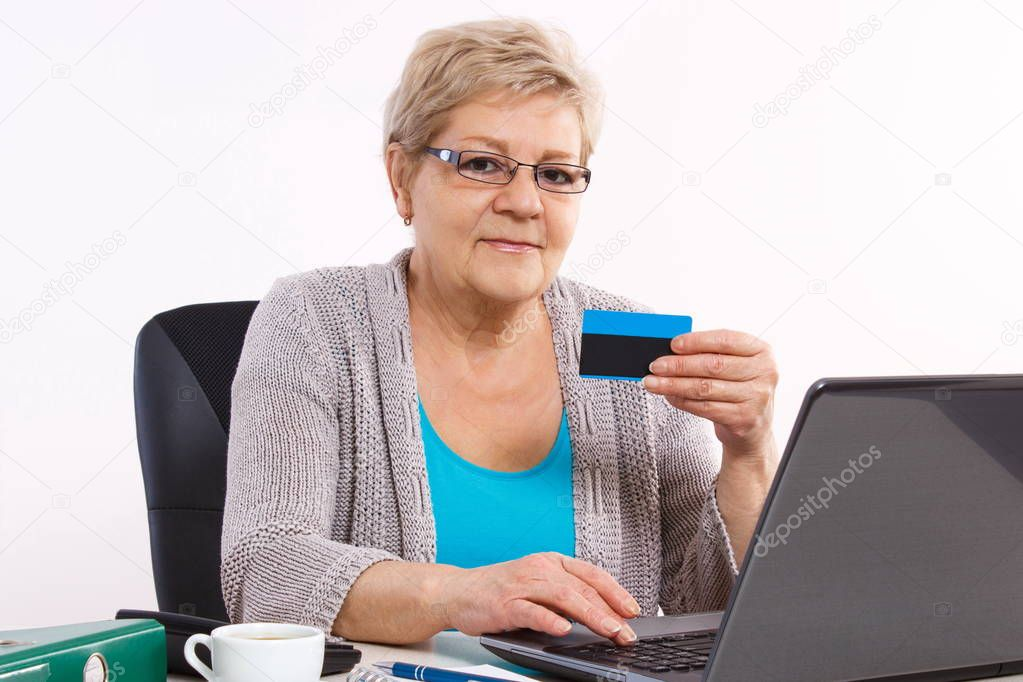 Elderly senior woman with credit card and laptop paying over internet for utility bills or online shopping