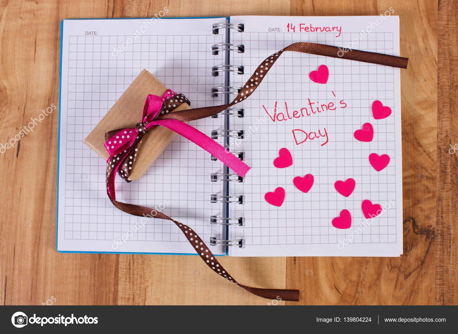 Saint Valentin écrit dans le cahier, enveloppé cadeau et les cœurs
