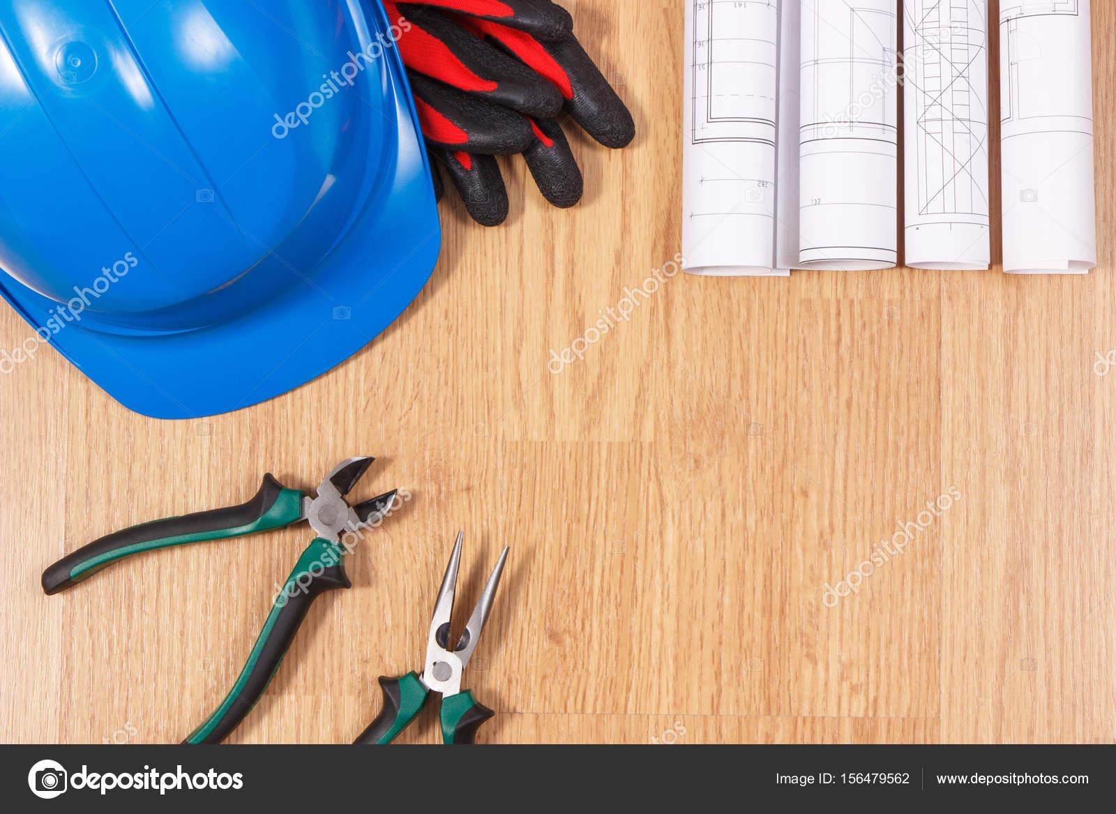 c2851072920d2 Rouleaux de diagrammes et dessins de construction électrique, casque de protection  bleu avec des gants et une pince métallique, accessoires pour les travaux  ...