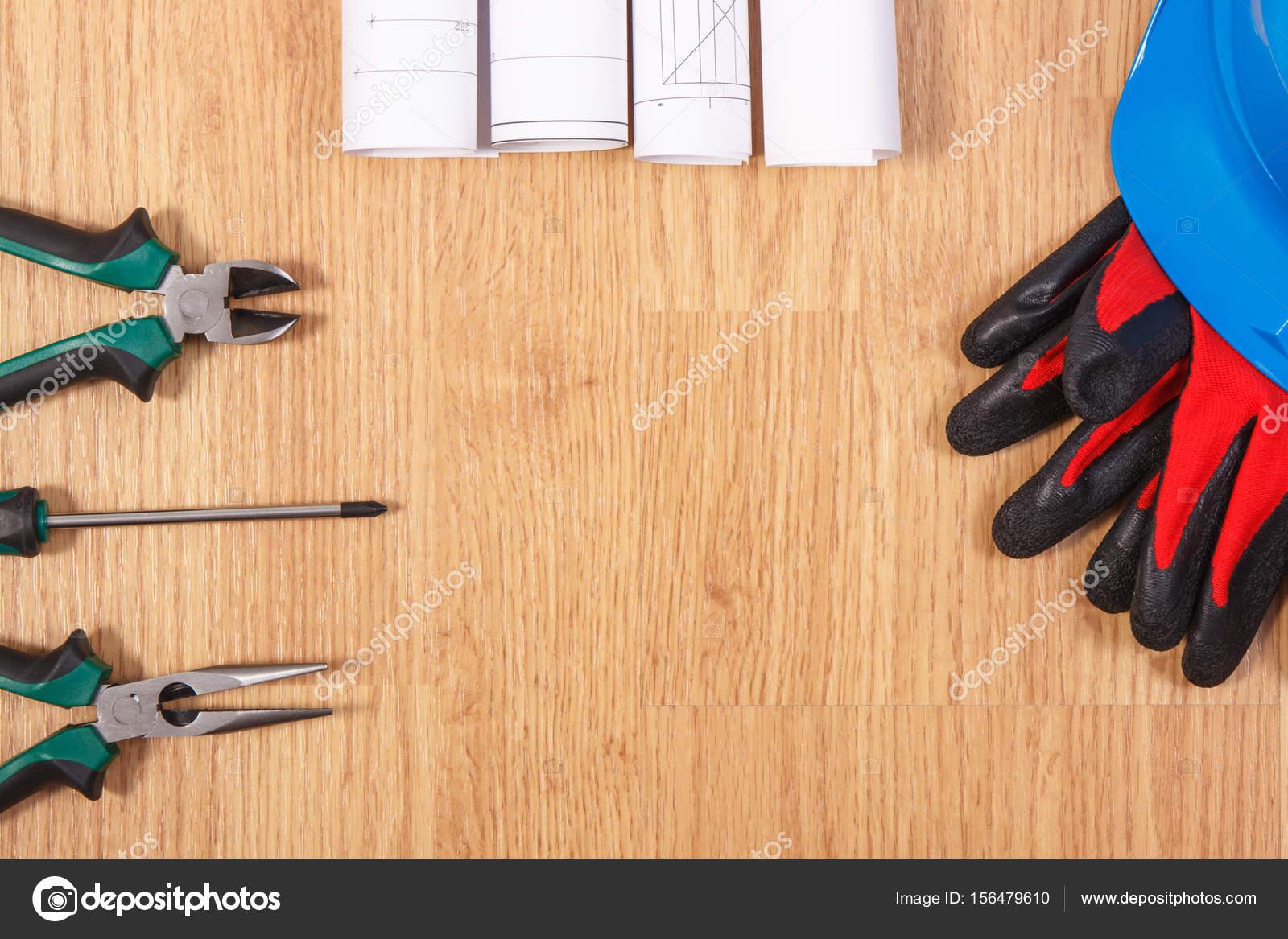 Rollen der Schaltpläne oder Baupläne, Schutzhelm mit Handschuhen und ...