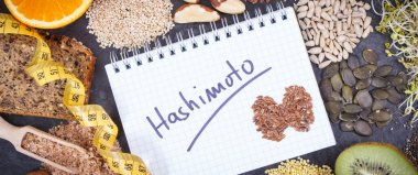 Tape measure, notepad with inscription hashimoto and best nutritious ingredients for healthy thyroid. Dieting and slimming concept