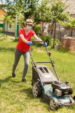 A woman in her backyard mowing grass with a lawn mower on a sunny day at home wearing a surgical mask because of the coronavirus epidemic.