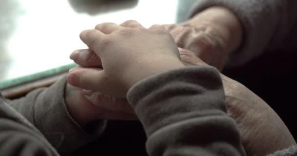 Hand in Hand. die Hand eines Kindes, das eine alte streichelt... Mitgefühl, Generationenverbindung, Fürsorge und Zuneigung, die Aufmerksamkeit des Kindes für die Alten. Coronavirus, Pandemie, Schutz der Alten